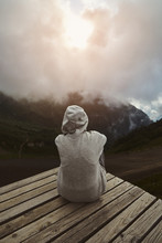 A Girl In A Grey Hoodie Sitting On A Viewpoint And Watching Sunset In The Mountains