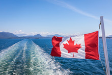 A Close Up Of The Canadian Flag Flying In The Wind At The Back Of Ferry As The Boat Makes It Way Through The Inside Passage, British Columbia, Canada