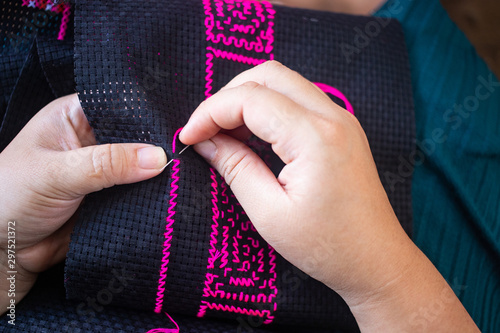 Fotografie, Obraz  Close up hands doing cross stitch using pink threads on black cloth