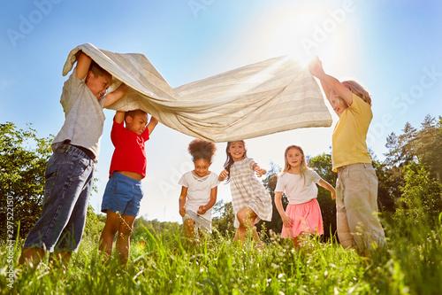 Gruppe Kinder spielt zusammen mit einem Tuch Wallpaper Mural