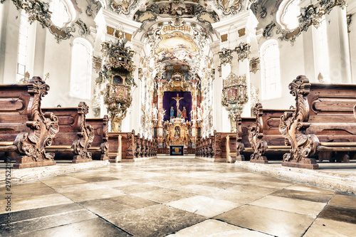 Leinwand Poster  WIESKIRCHE, GERMANY – MARCH 07: View on rococo interior of chapel with benches on March 07, 2016 in Wieskirche, Germany