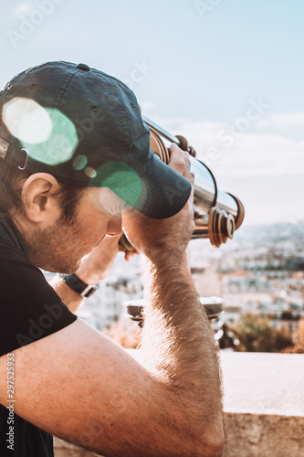 A man in a cap looks at the panorama of the city from the observation deck Tablou Canvas