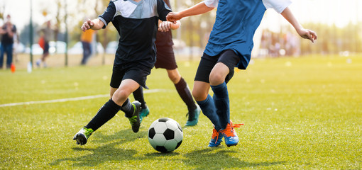 Two soccer players running and kicking a soccer ball. Legs of two young football players on a match. European football youth player legs in action