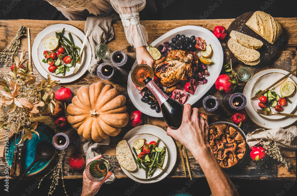Fototapety, obrazy: Thanksgiving party table setting. Flat-lay of people pouring champagne and celebrating at table with roasted chicken, vegetables, fig pie, fruit, candles over wooden table background, top view