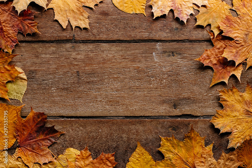 Fotografija  Autumn leaves on wooden background with copy space