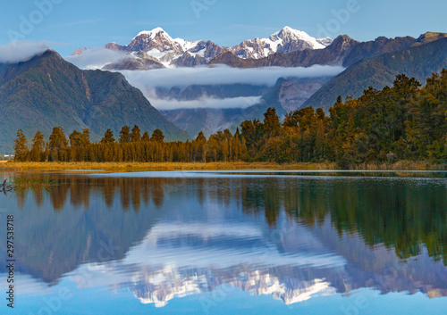 Poster Alpes Scenic view of Lake Matheson near the Fox Glacier with reflected views of Aoraki Mount Cook and Mount Tasman in South island, New Zealand, The place of tourist attraction and famous of New Zealand.