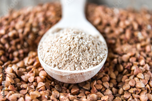 Fényképezés  Buckwheat flour in a wooden spoon on a pile of roasted buckwheat