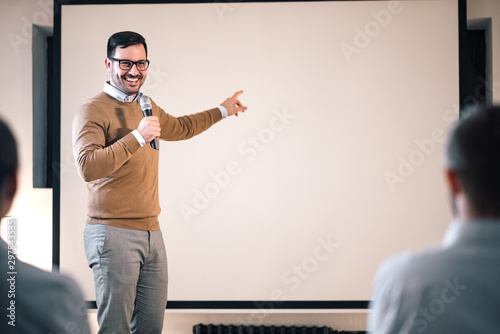 Stampa su Tela Portrait of a speaker on a seminar, talking on microphone and pointing at blank screen