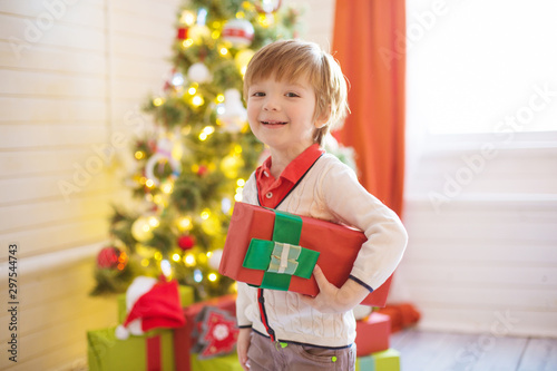 Autocollant pour porte Kiev Little boy hold a gift box near a decorated Christmas tree at home