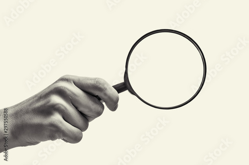 Female hand holding the magnifying glass on isolated background Wallpaper Mural