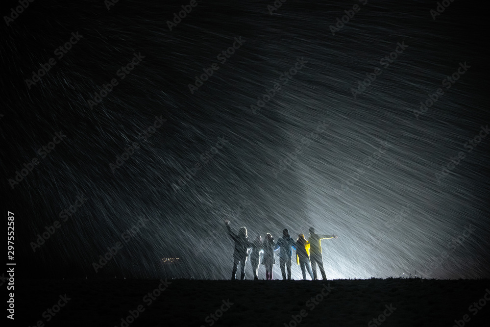 Fototapety, obrazy: Group of silhouettes against snowfall and back light