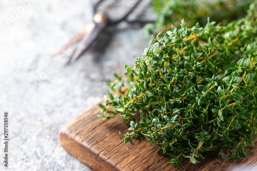 Fotografering Bunch of fresh thyme herb on old wooden board