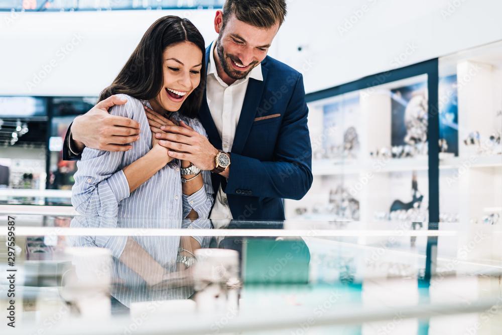 Fototapeta Beautiful couple enjoying in shopping at modern jewelry store.