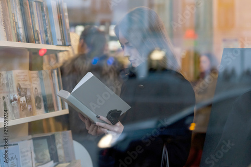 Photographie Beautiful girl reading a book in a bookstore