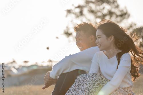 Photo  陽の当たる広場で遠くを見つめるカップル