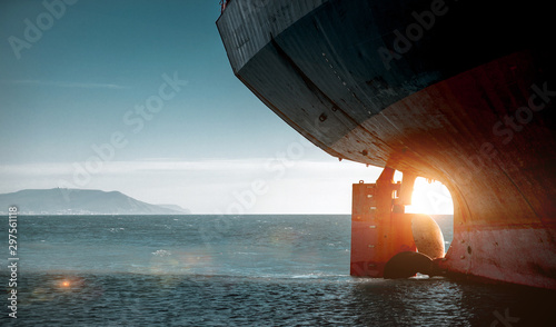 Photo Stern of a cargo ship aground against backdrop of blue sea