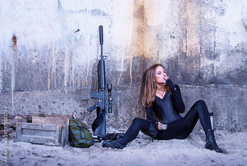 Photo A badass lady in a black catsuit smokes a cigarette while sitting near her combat equipment