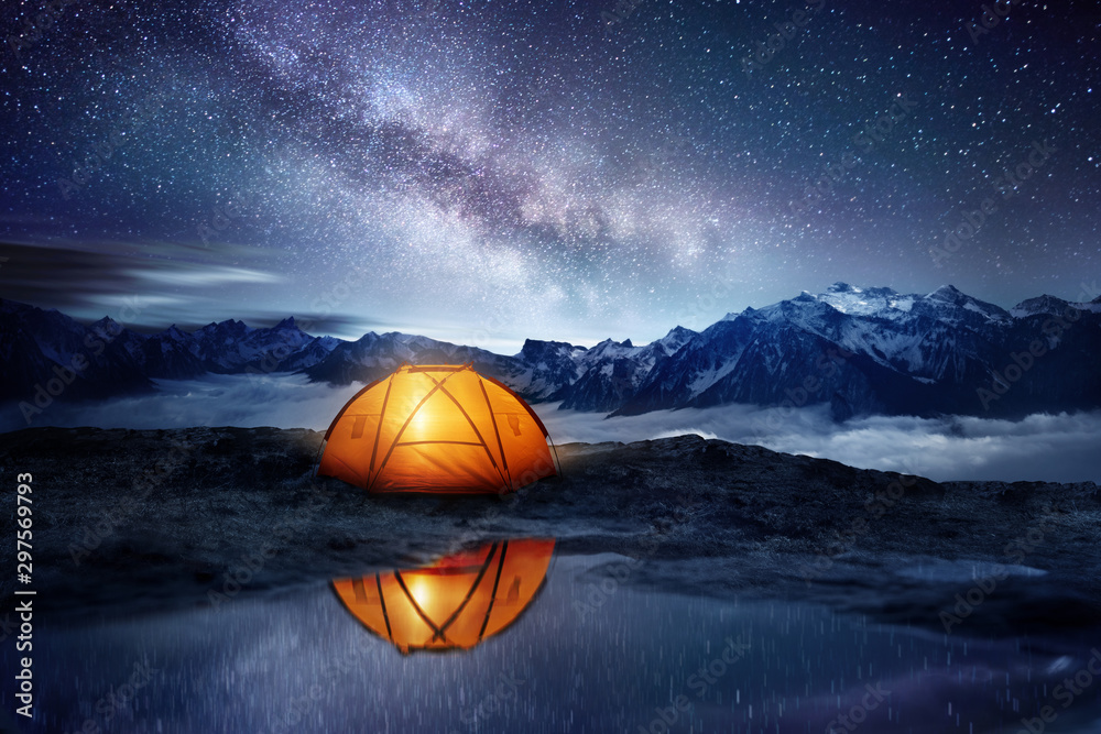 Fototapety, obrazy: Camping adventure in the mountains. A tent pitched up and glowing under the milky way. Photo composite.