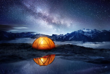 Camping Adventure In The Mountains. A Tent Pitched Up And Glowing Under The Milky Way. Photo Composite.