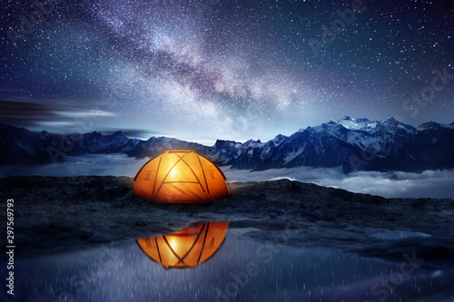 Spoed Fotobehang Kamperen Camping adventure in the mountains. A tent pitched up and glowing under the milky way. Photo composite.