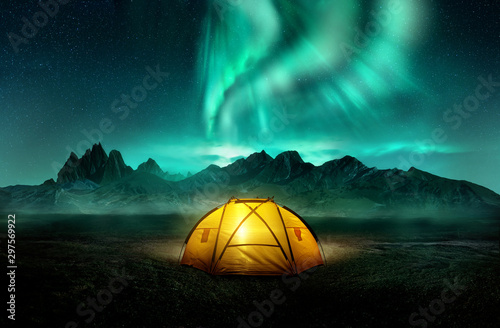 Spoed Foto op Canvas Kamperen A glowing yellow camping tent under a beautiful green northern lights aurora. Travel adventure landscape background. Photo composite.