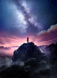 canvas print picture - Night sky long exposure landscape. A man standing on a high rock watching the stars rise into the night sky. Photo composite.
