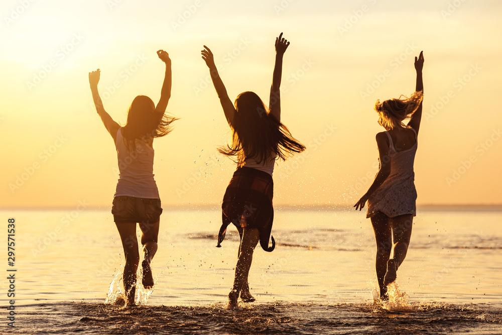 Fototapety, obrazy: Three happy girls at caml sea beach and sunset