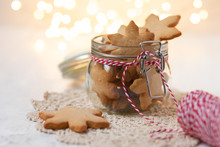 Delicious Sweet Christmas Gingerbread Cookies In Glass Jar Decorated With Red Ribbon. Best Homemade Present For Family! Lights On Background, White Table.