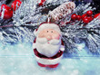 christmas santa on fir tree branch with cones and snow on background