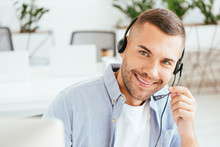 Selective Focus Of Happy Operator In Brokers Agency Touching Headset And Looking At Camera In Office