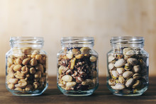 Three Glass Jars With Mixed Nuts And Dried Fruits