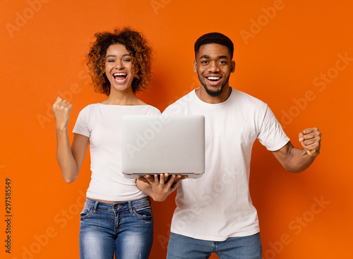 Cheerful black millennial couple with laptop screaming Fototapete
