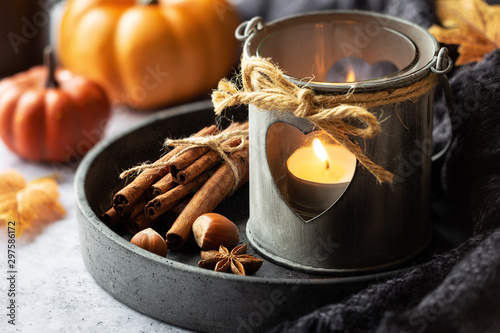 Fototapeta Autumn or fall concept with a romantic shabby chic lantern, aromatic spices, autumnal leaves and pumpkins at the background