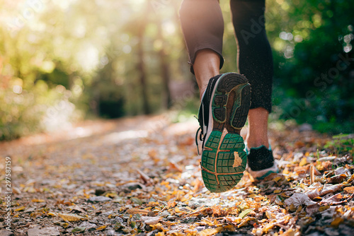 Closeup of running shoe of the person running in the nature with beautiful sunlight Fototapete
