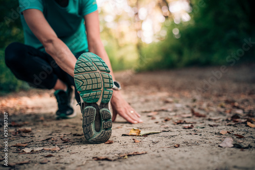 Active girl doing stretching before her jogging in the nature. Wallpaper Mural