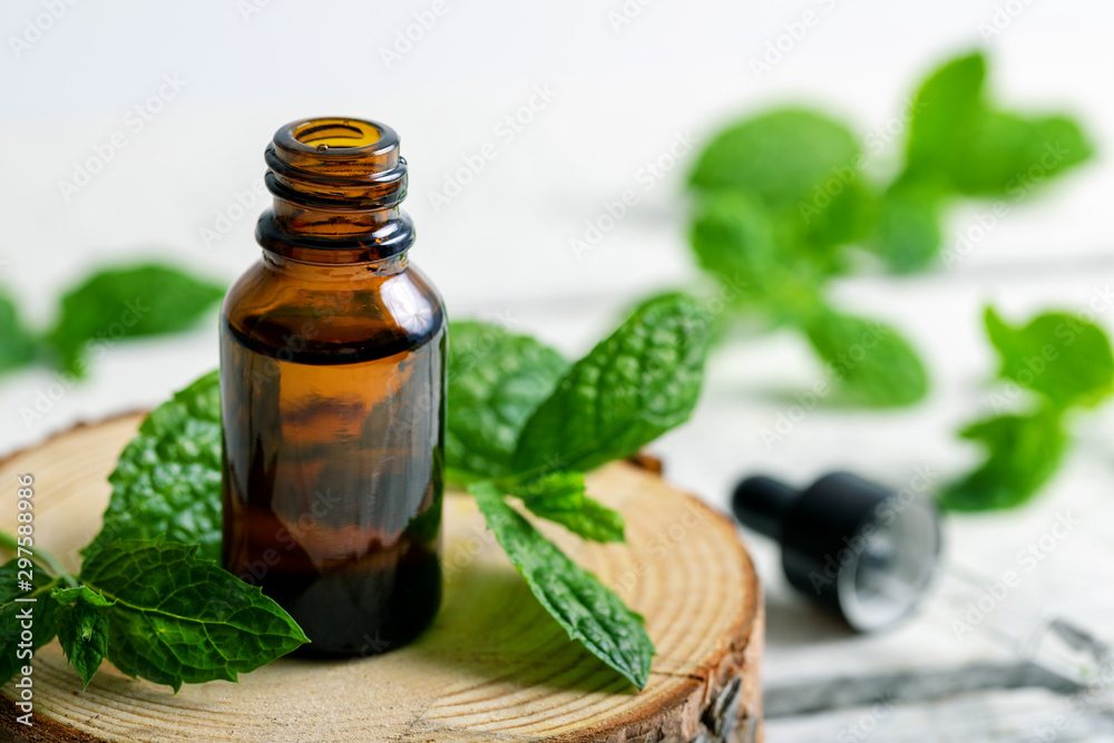 Fototapety, obrazy: mint essential oil bottle with green leaf on wooden pad