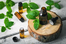 Aromatherapy Treatment - Essential Oil Bottles With Mint Leaves On White Wooden Background