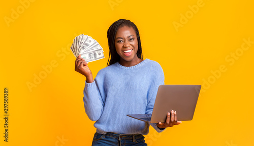 Valokuva African american young woman making money from internet, using laptop