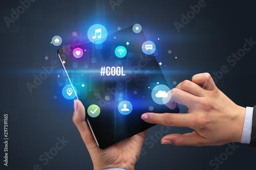Valokuvatapetti Businessman holding a foldable smartphone with #COOL inscription, social media c
