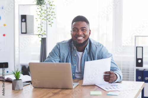 Photo Cheerful afro businessman working with laptop and documents in office