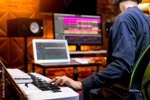 male producer, musician, composer making a song in home recording studio. music production concept - 297593177