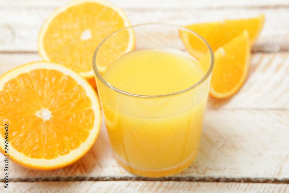 Fototapeta Orange juice in a glass, oranges and orange slices on the table.
