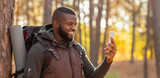 African man taking photos of beautiful autumn forest