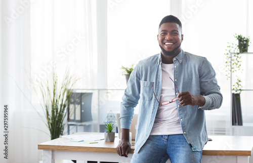 Fotografía  Successful businessman leaning on office desk and looking at camera