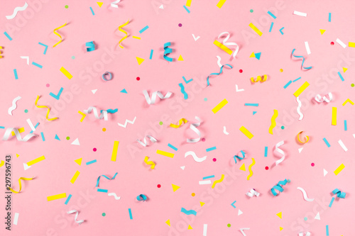 Colorful paper confetti exploding on pastel pink background