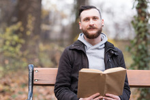 Hipster Man Reading On A Bench