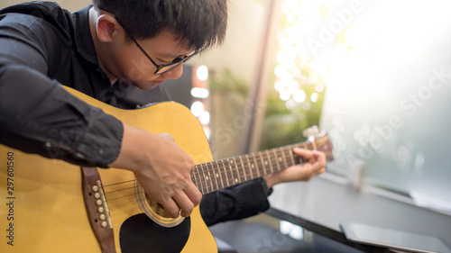 Young Asian man guitarist playing music with classic guitar at home. String musical instrument for recreational activity or personal hobby. Relaxation and entertainment concepts - 297601560