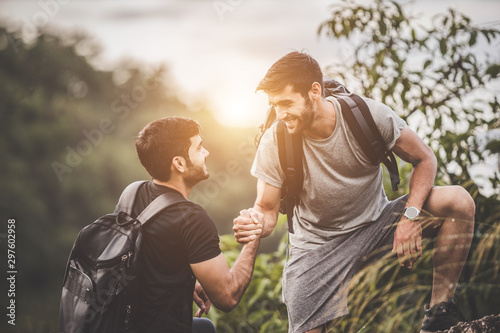Adventure themed travel and hiking trips - Friends helping each other to climb the mountain intently Fototapet
