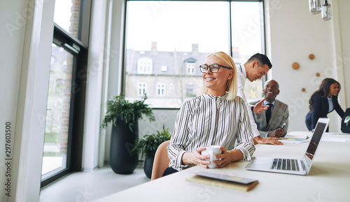 Stampa su Tela  Smiling young businesswoman enjoying her coffee during an office