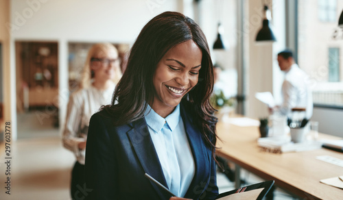 Fotomural  African American businesswoman smiling while walking in an offic